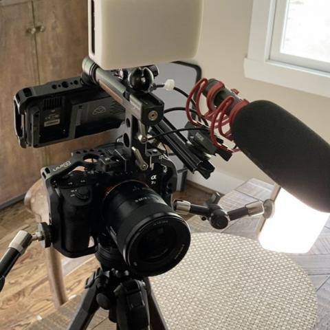 Part of the custom video camera setup, showing a tripod with a camera and boom mic on a table